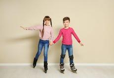 Muchacho y muchacha lindos con los pcteres de ruedas fotografía de archivo libre de regalías