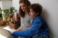 Muchacho y muchacha lindos que usa el ordenador portátil junto en casa Imagenes de archivo