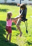 Muchacho y muchacha mojados en un oscilación Foto de archivo libre de regalías