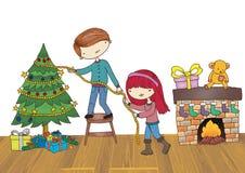 Muchacho y muchacha que adornan el árbol de navidad Foto de archivo libre de regalías