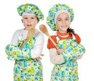 Muchacho y muchacha que aprenden cocinar Imágenes de archivo libres de regalías