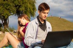 Muchacho y muchacha que aprenden en parque con el ordenador portátil y la tableta Imágenes de archivo libres de regalías