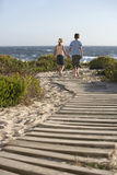 Muchacho y muchacha que caminan en paseo marítimo hacia el mar Imágenes de archivo libres de regalías