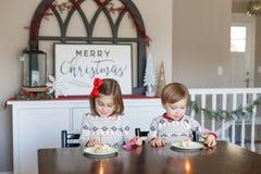Muchacho y muchacha que comen la torta para la Navidad imágenes de archivo libres de regalías