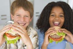 Muchacho y muchacha que comen las hamburguesas sanas Imagen de archivo