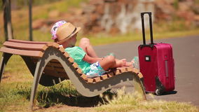 Muchacho y muchacha que descansan sobre un banco con una maleta metrajes