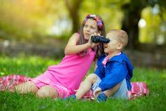 Muchacho y muchacha que exploran el ambiente con un binocular Imagen de archivo