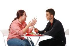 Muchacho y muchacha que hablan y que comen Imagen de archivo libre de regalías