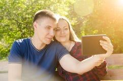 Muchacho y muchacha que hacen la sentada en banco en el selfie del parque en la tableta el día soleado del verano fotos de archivo libres de regalías
