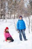 Muchacho y muchacha que juegan afuera en nieve Imagen de archivo libre de regalías