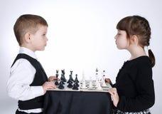 Muchacho y muchacha que juegan a ajedrez fotografía de archivo