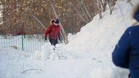 Muchacho y muchacha que juegan al aire libre en invierno Bolas de nieve del tiro de los niños almacen de metraje de vídeo