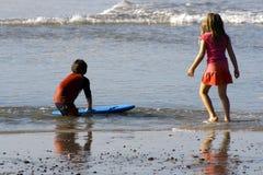 Muchacho y muchacha que juegan con agua. Foto de archivo libre de regalías