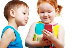 Muchacho y muchacha que juegan con el móvil Fotos de archivo