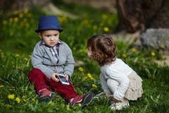 Muchacho y muchacha que juegan con el teléfono móvil Foto de archivo libre de regalías