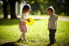 Muchacho y muchacha que juegan con la bola amarilla Fotografía de archivo libre de regalías