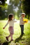 Muchacho y muchacha que juegan con la bola amarilla Imagen de archivo