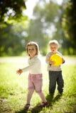 Muchacho y muchacha que juegan con la bola amarilla Fotos de archivo