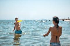 Muchacho y muchacha que juegan el disco volador en el agua Imagen de archivo