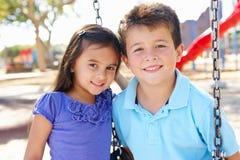 Muchacho y muchacha que juegan en el oscilación en parque Imagen de archivo libre de regalías