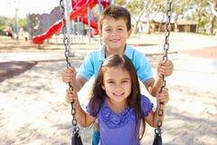 Muchacho y muchacha que juegan en el oscilación en parque Fotos de archivo