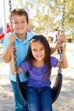 Muchacho y muchacha que juegan en el oscilación en parque Imagenes de archivo