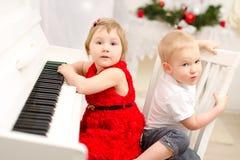 Muchacho y muchacha que juegan en el piano blanco imagenes de archivo