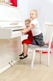 Muchacho y muchacha que juegan en el piano blanco fotografía de archivo libre de regalías