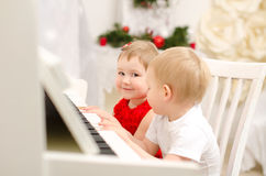 Muchacho y muchacha que juegan en el piano blanco foto de archivo