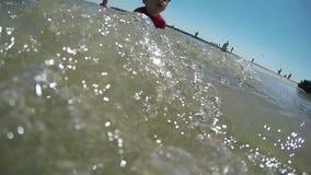Muchacho y muchacha que juegan en las ondas costeras almacen de video