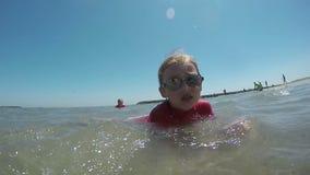 Muchacho y muchacha que juegan en las ondas costeras almacen de metraje de vídeo
