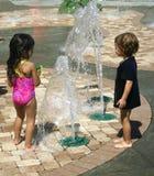 Muchacho y muchacha que juegan en piscina de agua Imagen de archivo