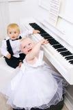 Muchacho y muchacha que juegan en un piano blanco Fotografía de archivo libre de regalías