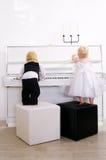 Muchacho y muchacha que juegan en un piano blanco Imagen de archivo libre de regalías