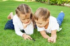 Muchacho y muchacha que juegan en un teléfono móvil Imágenes de archivo libres de regalías