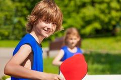 Muchacho y muchacha que juegan junto al ping-pong afuera Imágenes de archivo libres de regalías
