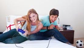 Muchacho y muchacha que juegan a los juegos video Foto de archivo libre de regalías