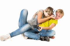 Muchacho y muchacha que juegan un videojuego y una lucha Fotografía de archivo