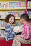 Muchacho y muchacha que leen junto Imagen de archivo