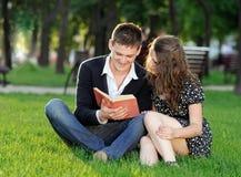 Muchacho y muchacha que leen un libro que se sienta en la hierba Fotos de archivo libres de regalías