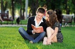 Muchacho y muchacha que leen un libro que se sienta en la hierba Fotografía de archivo