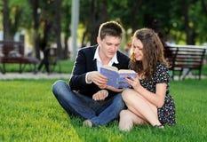 Muchacho y muchacha que leen un libro que se sienta en la hierba Imagen de archivo