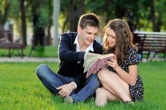 Muchacho y muchacha que leen un libro que se sienta en la hierba Imagenes de archivo