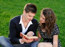 Muchacho y muchacha que leen un libro que se sienta en la hierba Imagen de archivo libre de regalías
