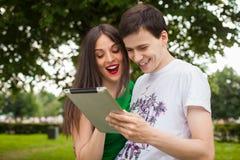 Muchacho y muchacha que llevan a cabo el ipad junto al aire libre en el parque imágenes de archivo libres de regalías