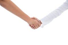 Muchacho y muchacha que mantienen la mano unida en blanco Foto de archivo