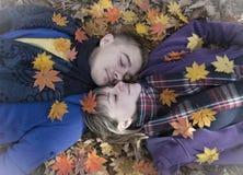 Muchacho y muchacha que mienten en las hojas de arce caidas Imagen de archivo