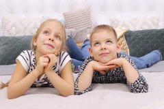 Muchacho y muchacha que mienten en una cama Una más vieja hermana And Her Younger Brother Dreaming imagenes de archivo
