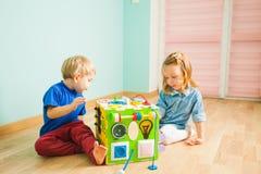 Muchacho y muchacha que miran el nuevo juguete interesante foto de archivo libre de regalías