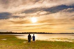 Muchacho y muchacha que miran puesta del sol fotografía de archivo